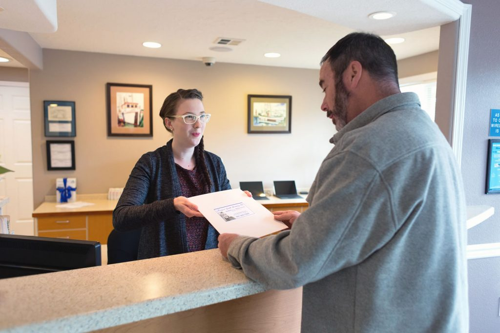 Receptionist Hands Dental Care Patient Paperwork at Our Newport Oregon Dentist Office
